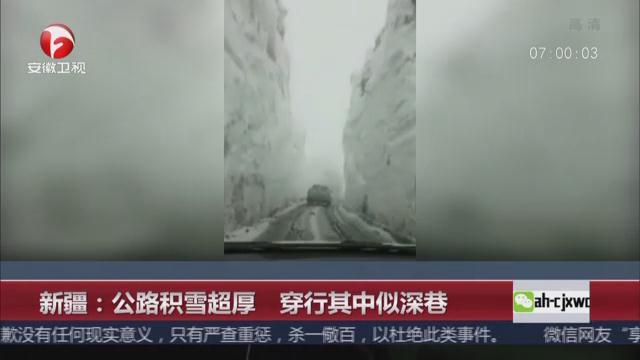 新疆公路积雪高度达三层楼 穿行其中似深巷
